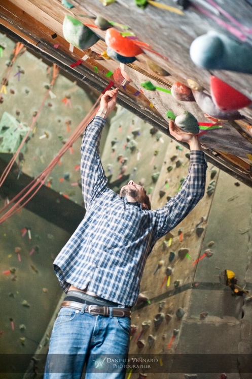 "Travis Gault, bossman, or ""Old Pappy"" as he likes to refer to himself, cleaning of a chalked up hold to allow for better grip for the next competitor during the Climbnasium Frostbite Climbing Comp 2012"