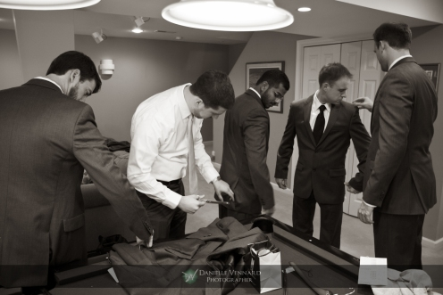 the groom and his groomsmen all helping one another to look their best