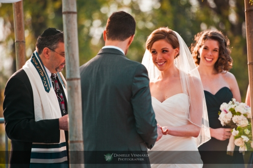 bride is all smiles as the groom puts on her ring