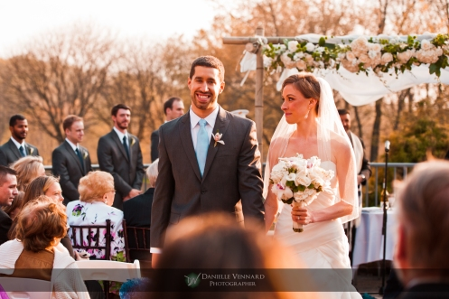 Bride glances at her new husband as they walk back down the aisle as man & wife