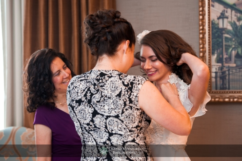 bride's sister putting on keepsake necklace as mom looks on in joy Copyright 2012 Danielle Vennard Photographer