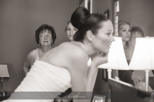 the mother and bridesmaid gazing at the bride while she puts on her finishing touches