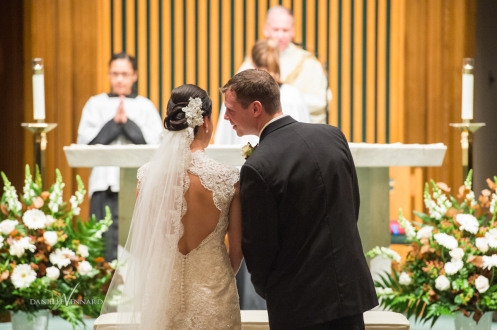 groom whispering into the brides ear during the ceremony