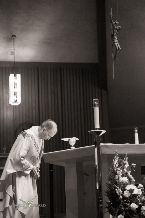 the priest praying at communion during a wedding ceremony at Lady Fatima Catholic church