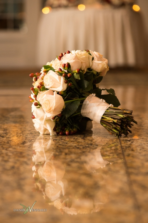 bride's bouquet full of white roses and red berries