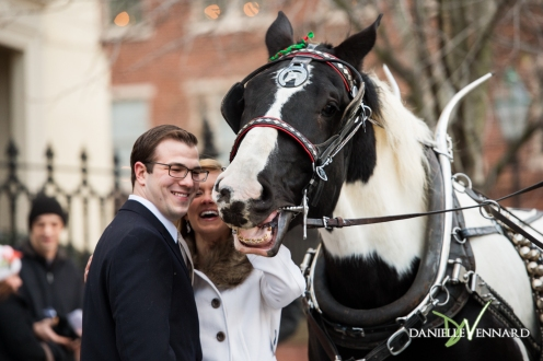 Engaged couple petting the horse that is part of the carriage rides in Bethlehem, pa