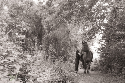 engaged couple walking through the tree line while bride to be is on her horse and groom accompanies beside them