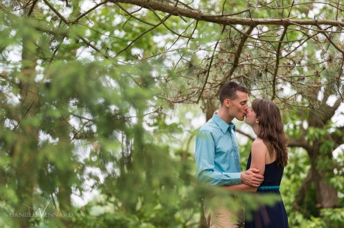 Engaged couple enjoying a kiss while surrounded by greens and browns of the woods