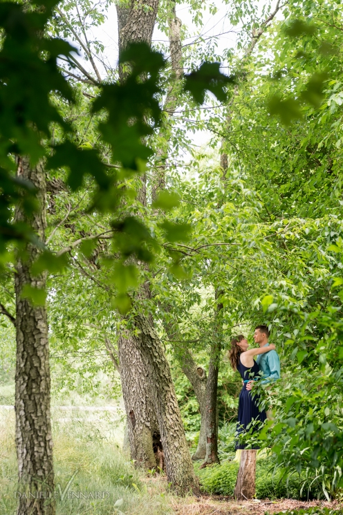 Engaged couple embracing while surrounded by the greens and browns of the woods