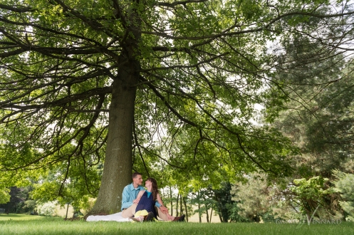 Engaged couple enjoying some shade under a huge leafy tree